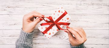 Woman hands give wrapped valentine or other holiday handmade present in paper with red ribbon. Present box, red heart of gift on. Table, Top view banner with stock photo