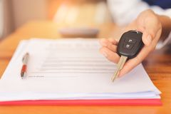 Woman hands giving a car remote key after signed contract agreement and successful deal. stock image