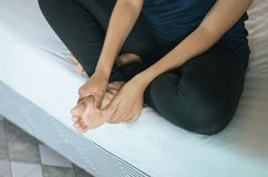 Woman hands giving massage to her foots in bedroom,foot soles massage. Woman hands giving massage to her foots in her bedroom,foot soles massage Royalty Free Stock Photos