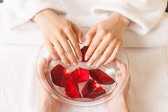 Woman hands in glass bowl with water on white towel. stock image
