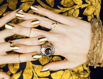 Woman hands with golden manicure lot of jewelry on fancy dress close up Royalty Free Stock Photo