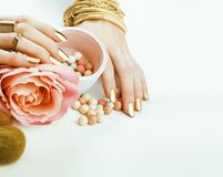 Woman hands with golden manicure many rings holding brushes, make up artist stuff stylish and pure. Woman hands with golden manicure and many rings holding stock image