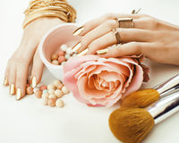 Woman hands with golden manicure and many rings holding brushes, makeup artist stuff stylish, pure close up pink Royalty Free Stock Image
