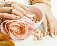 Woman hands with golden manicure and many rings holding brushes, makeup artist stuff stylish, pure close up pink flower Stock Photo