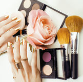 Woman hands with golden manicure and many rings holding brushes, makeup artist stuff stylish, pure close up pink flower Stock Photography