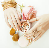 Woman hands with golden manicure and many rings holding brushes, makeup artist stuff stylish, pure close up pink Stock Photo