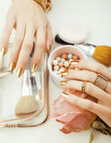 Woman hands with golden manicure and many rings holding brushes, makeup artist stuff stylish, pure close up pink Royalty Free Stock Photos