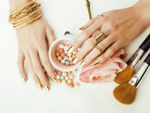 Woman hands with golden manicure and many rings holding brushes, makeup artist stuff stylish, pure close up pink Stock Image