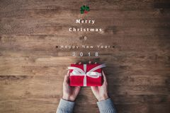 Woman hands holding red gift box on a table with Merry Christmas and Happy New Year 2018 texts Stock Image