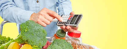 Woman hands with grocery food and calculator. Stock Photo