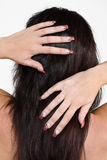 Woman hands on hair. A studio view of the back of a woman with manicured fingernails, running her hands through her long black hair.  White background Stock Photography