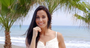 Woman with Hands in Hair on Tropical Beach. Attractive Smiling Brunette Woman Smiling at Camera with Hands in Hair on Tropical Beach with Palm Trees stock footage