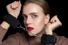 Woman hands are handcuffed. Beautiful girl with a very triple face feels real fear because her hands are handcuffed for role-playing. Dominate, obey to master stock image