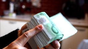 Woman hands handling a wad of hundred-euro bills. stock video footage