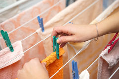 Woman hands hanging clothes to dry on clothes-line after laundry.  Royalty Free Stock Image