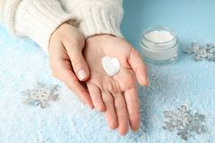 Free Woman Hands, Heart Shape Created From Winter Cream, Jar Of Winter Cream For Skin On Snowy Blue Background Stock Photos - 164905783