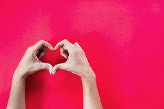 Woman hands with heart shape on red background. With copy space Stock Images