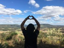 Woman, hands, heart, sky, mountains, trees. Guy Hands is heart-shaped air-standing mountain in the sky, a happy Valentine`s Day.love nature Royalty Free Stock Photos