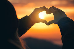 Woman hands Heart symbol shaped silhouette. Travel Lifestyle and Feelings concept with sunset sky nature on background Stock Photos