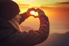 Woman hands Heart symbol shaped Travel Lifestyle. And Feelings concept with sunset sky nature on background Stock Images