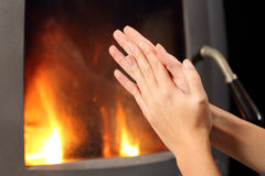 Woman hands heating in front a fire place. Woman rubbing hands and heating in front a fire place at home in winter Stock Images