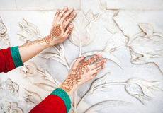 Woman hands in henna painting in India. Woman in red Indian costume touching white marble wall with floral pattern by hands in henna painting in Taj Mahal in Royalty Free Stock Photo