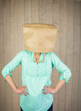 Woman with hands on hip and covering head with brown paper bag Stock Photo