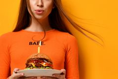 Woman hands hold big burger barbeque sandwich with beef and lit candle for birthday party on yellow. Woman hold big burger barbeque sandwich with beef and lit Royalty Free Stock Image