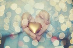 Woman hands are holding a beautiful glossy gold heart in a snow winter background. Love and St. Valentine cozy concept.