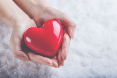 Woman hands are holding a beautiful glossy red heart in a snow background. Love and St. Valentine concept. Stock Image