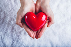 Woman hands are holding a beautiful glossy red heart in a snow background. Love and St. Valentine concept. Stock Images