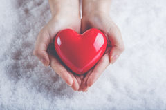 Woman hands are holding a beautiful glossy red heart in a snow background. Love and St. Valentine concept. Royalty Free Stock Photo