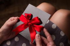 Woman hands holding a black paper card with red textile ribbon Royalty Free Stock Photos