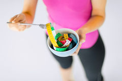 Woman hands holding bowl with measuring tape Royalty Free Stock Image