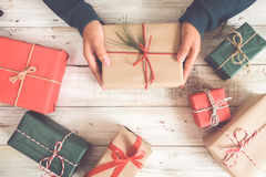 Woman hands holding a Christmas gift with a red ribbon Royalty Free Stock Image