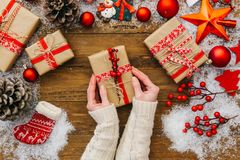 Woman hands holding Christmas present. Wooden background royalty free stock photo