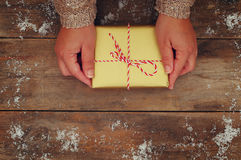Woman hands holding Christmas presents on a wooden table stock photo