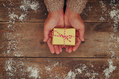 Woman hands holding Christmas presents on a wooden table royalty free stock photo
