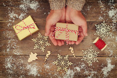 Woman hands holding Christmas presents on a wooden table Royalty Free Stock Photos