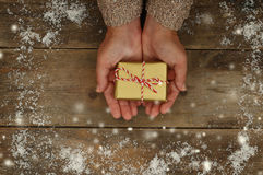 Woman hands holding Christmas presents on a wooden table Royalty Free Stock Images