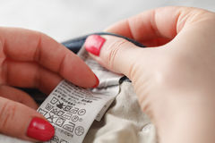Woman hands holding clothes label with cleaning instructions Royalty Free Stock Photo