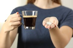 Woman hands holding a coffee cup and saccharin pills. Front view close up of a woman hands holding a coffee cup and saccharin pills Stock Photo