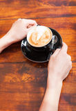 Woman hands holding coffee on wooden table Stock Photography