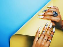 Woman hands holding colorful paper copyspace wearing a lot of jewelry rings and long nails manicure royalty free stock photos
