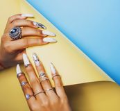 Woman hands holding colorful paper copyspace wearing a lot of or. Iental jewelry rings, indian girl concept close up stock photos