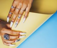 Woman hands holding colorful paper copyspace wearing a lot of or. Iental jewelry rings, mulatto indian girl concept close up royalty free stock image