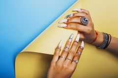 Woman hands holding colorful paper copyspace wearing a lot of or. Iental jewelry rings, mulatto indian girl concept close up stock images