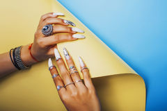 Woman hands holding colorful paper copyspace wearing a lot of oriental jewelry rings, mulatto indian girl concept. Close up stock image