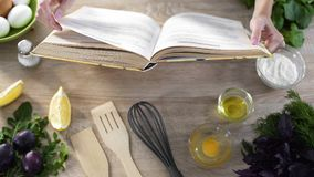Woman hands holding cooking book table, girl choosing recipe for family dinner. Stock footage Stock Image