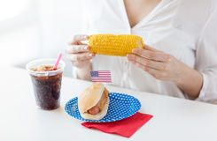 Woman hands holding corn with hot dog and cola. American independence day, celebration, patriotism and holidays concept - close up of woman hands holding corn Stock Photo
